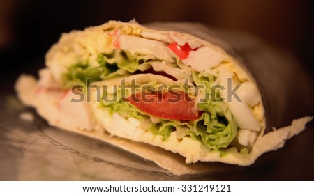 roll of pita with lettuce,eggs and tomatoes