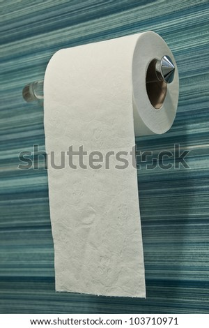 roll of toilet paper on blue striped background tiles