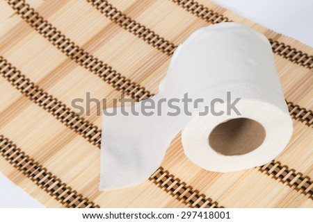 Roll of toilet paper on brown background. - stock photo