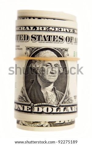 Roll of U.S. banknotes on plain background