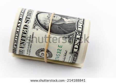 Roll of U.S. banknotes rolled up on plain background