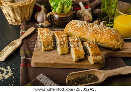 Roll out puff pastry stuffed with mushrooms, cheese and ham