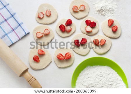 Roll out the dough on the kitchen table. - stock photo