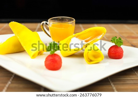 roll pancake mango with mango juice on black background. , depth of field or dof picture - stock photo
