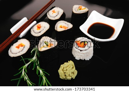 Roll with Cucumber , Cream Cheese with raw Tuna and Salmon inside. on black wooden plate. Japanese traditional Cuisine - stock photo