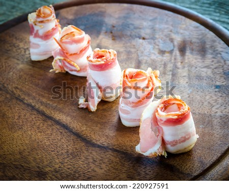 Rolled bacon strips on wooden board - stock photo