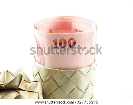 Rolled banknotes on weaved basket from natural material  - stock photo