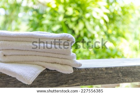 rolled beach or spa towels on natural green background - stock photo