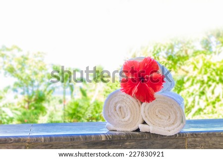 rolled beach or spa towels on natural tropical background - stock photo