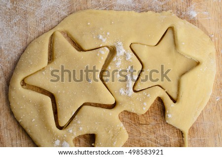 Rolled biscuit or cookie dough with star shapes cut out from the pastry on a floured old wooden chopping board.