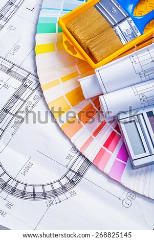 rolled blueprints and paint brushes in tray calculator on color palette  - stock photo