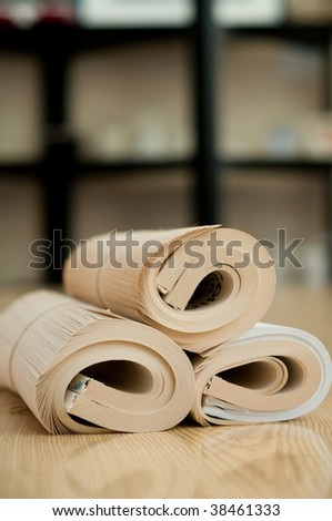 Rolled book on the wood table - stock photo