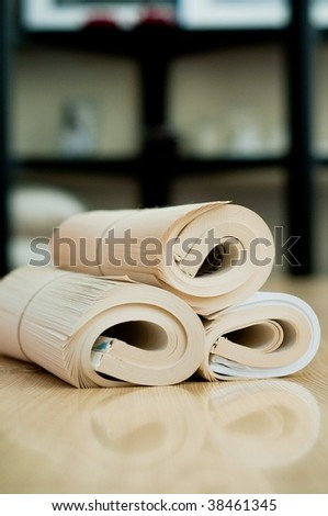 Rolled book with reflection on the wood table - stock photo