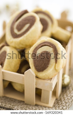 Rolled cookies in wood tray - stock photo