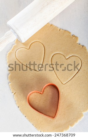 rolled dough with heart-shaped cookie cutter and rolling pin, valentine's day concept
