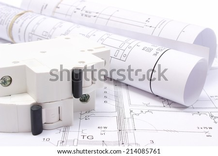 Rolled electrical diagrams and electric fuse lying on construction drawing of house, drawings for the projects engineer jobs - stock photo