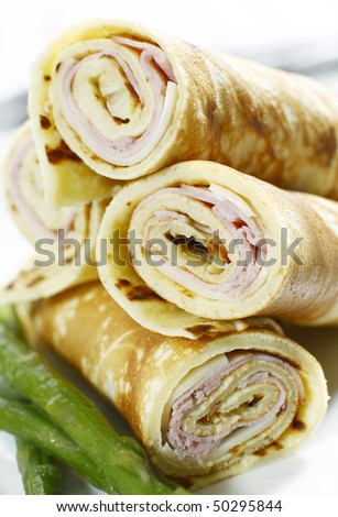 rolled ham and cheese crepe with asparagus on a white background. - stock photo
