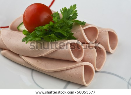 rolled ham on plate served with tomatoes - stock photo