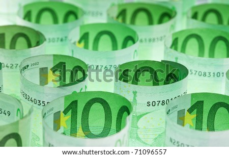Rolled hundred euro banknotes green money background - stock photo