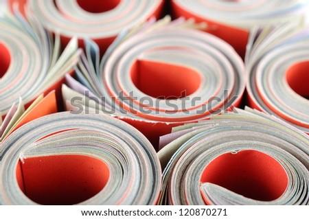 Rolled magazine background - stock photo
