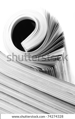 Rolled magazine on magazine stack. B&W image. - stock photo