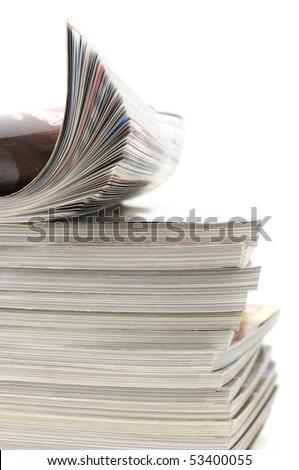 Rolled magazine on stack of magazines isolated on white background. - stock photo