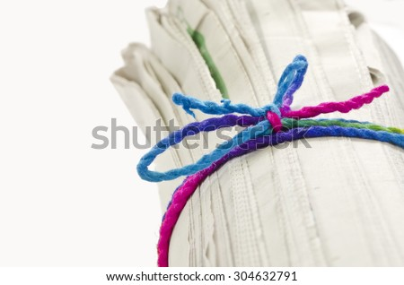Rolled newspaper with color rope on white background. - stock photo