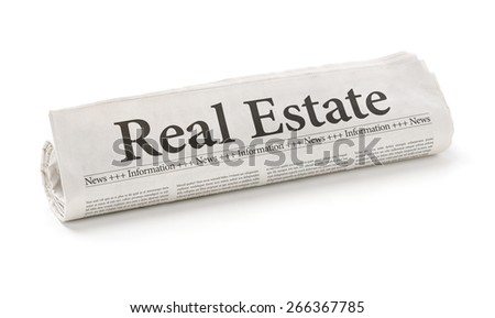 Rolled newspaper with the headline Real Estate - stock photo