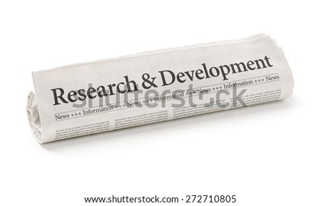 Rolled newspaper with the headline Research and Development - stock photo