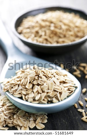 Rolled oats heaped on a spoon and whole oat groats - stock photo