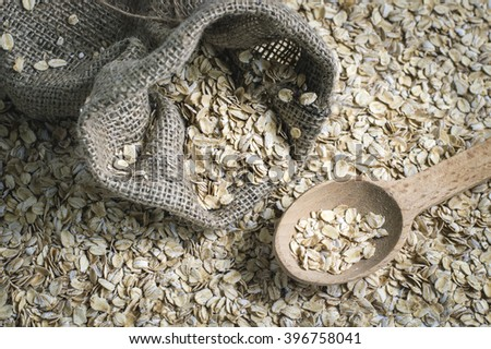 Rolled oats in a bag in a wooden spoon - stock photo