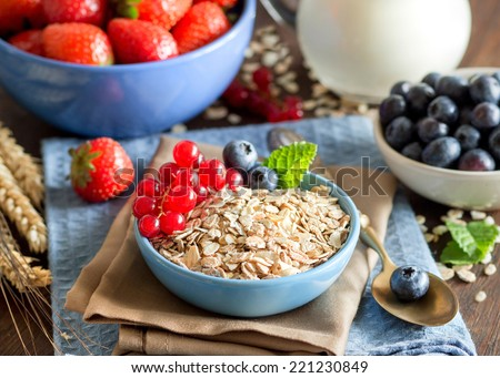 Rolled oats in a blue bowl on a napkin with berries, milk and spoon - stock photo