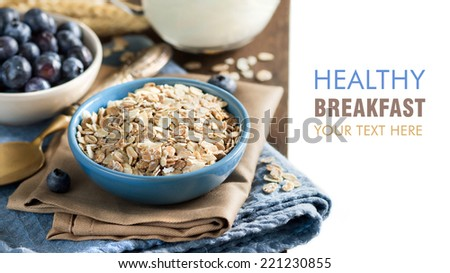 Rolled oats in a blue bowl on a napkin with blueberries, milk and spoon - stock photo
