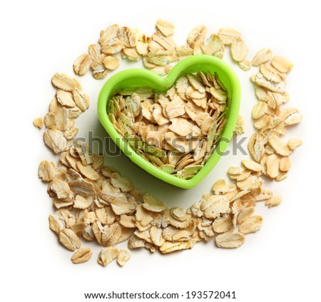 Rolled oats in green heart form - stock photo