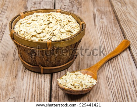 rolled oats in wooden bowl with spoon on old plank table