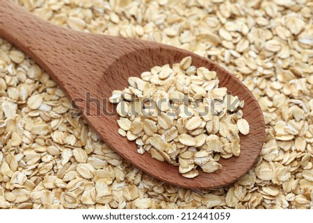 Rolled oats (oat flakes) in a wooden spoon on a rolled oats background. Close-up. - stock photo
