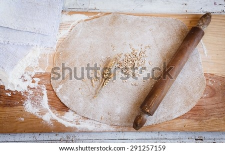 Rolled out wholemeal dough, wheat, grain with vintage rolling pin and linen napkin on the rustic table from above with copy text. Shabby chic and all-purpose for baking image. Creative rustic image