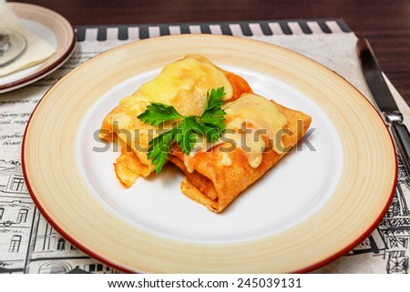 Rolled pancakes on plate with leaf of parsley - stock photo