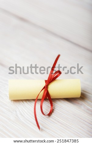Rolled paper with red ribbon on white vintage wooden background