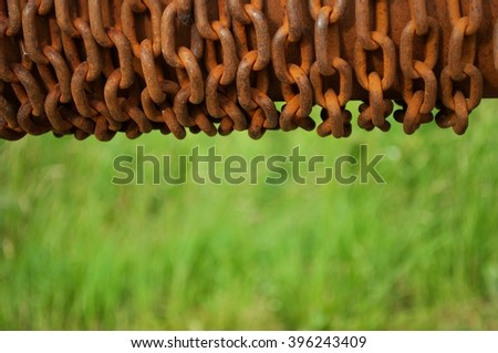 Rolled rusty chain with blurred green natural background. Space in bottom part of image - stock photo