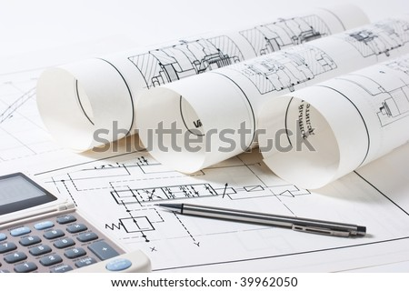 rolled technical drawings and a calculator - stock photo