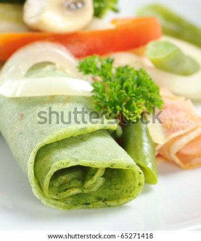 Rolled thin green colored pancake (colored with spinach in dough) with vegetables on top (Selective Focus, Focus on the front of the pancake) - stock photo
