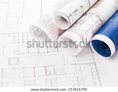 Rolled-up blueprints and house plans with copyspace