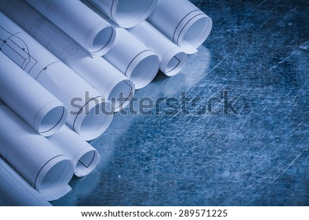 Rolled up blueprints on scratched vintage metallic background construction concept. - stock photo