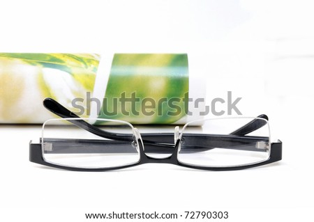 Rolled up colorful magazine and black colored glasses over white background - stock photo