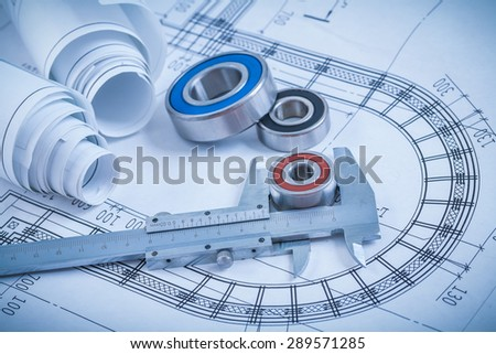 Rolled up construction plans roller bearings and slide caliper on blueprint industrial concept. - stock photo