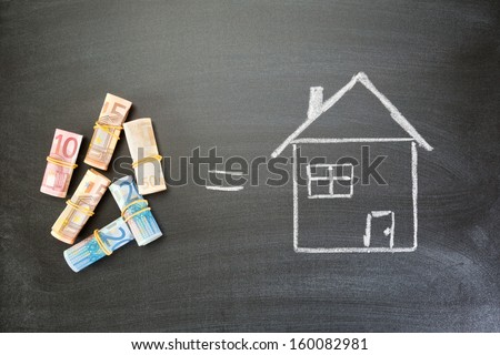 Rolled up Euro bills next to a hand drawn house on a blackboard with an equals sign between them, top view. - stock photo