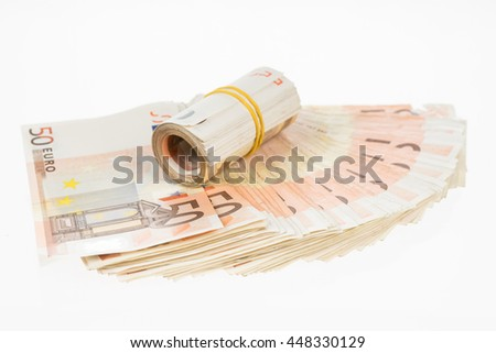 Rolled up euros with rubber on the fifty euro banknotes fan. Money bunch stack - stock photo