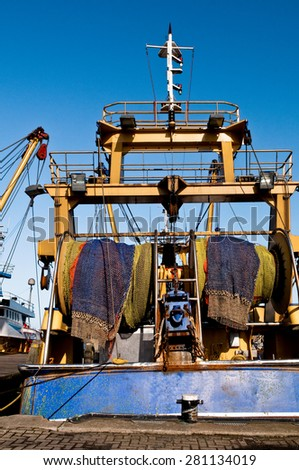 rolled up fishing nets on a fishing trawler - stock photo