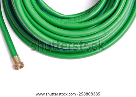 Rolled up garden new green garden hose top frame border isolated on white - stock photo